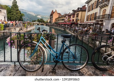 Annecy, France - August 8, 2018. View of french medieval Annecy old town with bicycle, canal and mountain view. Thiou river in Venice of the Alps, blue bike and ancient stone bridge.