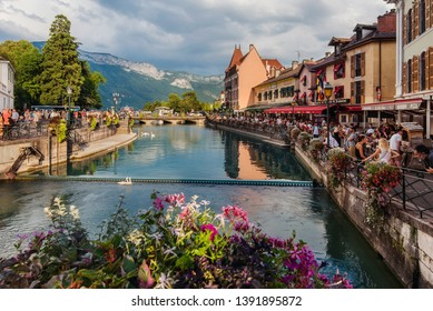 Annecy, France - August 8, 2018. View of french medieval Annecy old town with flowers on bridge, canal and mountain view. Thiou river in Venice of the Alps promenade.
