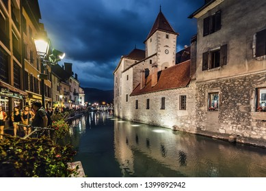 Annecy, France - August 8, 2018. View of Annecy old town with Thiou river, palace I'lle, medieval building facades with evening illumination reflected in canal water. Castle stone walls side view.