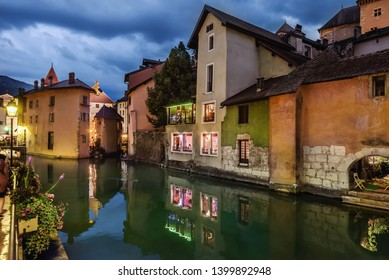 Annecy, France - August 8, 2018. View of french Annecy old town with Thiou river, palace I'lle, medieval building facades and cafes with evening illumination reflected in canal water.