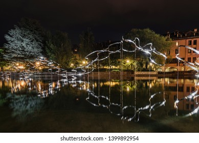 Annecy, France - August 8, 2018. Night view of metal installation in Annecy's Thiou river canal in Haute-Savoie region. Illuminated art object for Annecy paysages festival reflected in water.