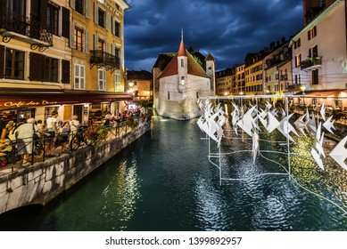 Annecy, France - august 8, 2018. View of Annecy old town with Palace I'lle on Thiou river, medieval buildings and cafes with night illumination. Cloud of origami fishes over canal near promenade.