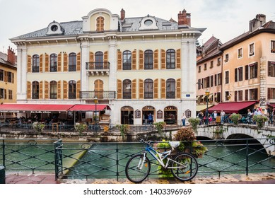 Annecy, France - August 9, 2018. View of french medieval Annecy old town promenade with bicycle, old building facades, stone bridge with flowers in pots and Thiou river canal.