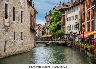 Annecy, France - august 9, 2018. View of Annecy old town with Thiou river canal, palace I'lle stone walls, medieval building facades with traditional french window shutters, flowers and cafe on bank.