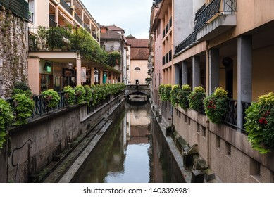 Annecy, France - August 9, 2018. View of french Annecy old town with Thiou river canal, medieval building facades, stone bridges and flowers in pots on medieval houses. Overcast day without people.