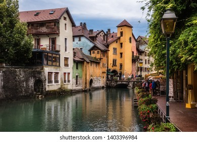 Annecy, France - August 9, 2018. View of french Annecy old town with Thiou river canal, medieval building facades, retro lanterns, stone bridge and flowers in pots on bank. Overcast day scenic view.