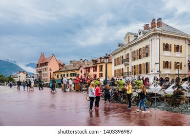 Annecy, France - august 9, 2018. People on promenade in french medieval Annecy's old town with view of colorful building facades, Thiou River canal and French Alps by rainy day.