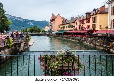 Annecy, France - August 9, 2018. View of french medieval Annecy old town promenade with colorful building facades, cafes, walking people, flowers on bridge, Thiou river canal and French Alps.