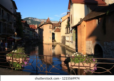 Annecy, France - August 9th 2013: Crowds of tourists streaming next to the embanked river Thiou through the lovely town of Annecy