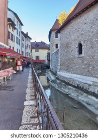 """Annecy, France - December 07, 2018: The """"Palais de l'Ile"""" in Annecy, a historical building placed in a small island on the river Thiou, which runs inside Annecy. The building was a prison"""