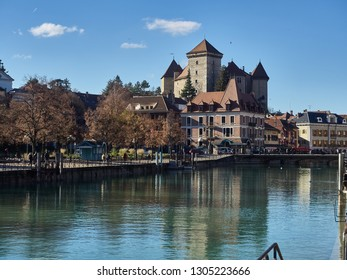 "Annecy, France - December 07, 2018: The river ""Le Thiou"", an effluent of the lake of Annecy, and the Castle in the background. The river runs along the ""Jardins de l'Europe"", a famous garden"