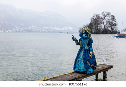 Annecy, France, February 23, 2013: Disguised person posing on a pier on Annecy Lake, during a Venetian Carnival which celebrates the beauty of the real Venice.