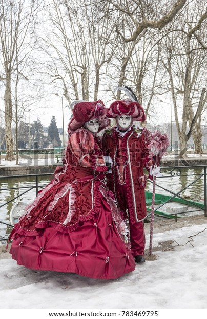 Annecy, France, February 23, 2013: A disguised couple posing in Annecy, France, during a Venetian Carnival which celebrates the beauty of the real Venice.