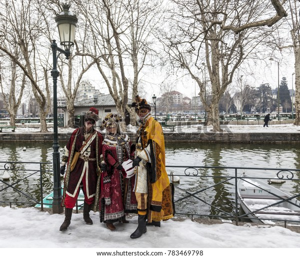 Annecy, France, February 23, 2013: A group of three disguised persons posing in Annecy, France, during a Venetian Carnival which celebrates the beauty of the real Venice.