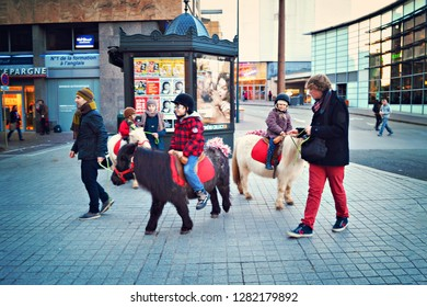 ANNECY, FRANCE - January 2016: The chieldren riding ponny on the street of Annecy at Christmas ave in Annecy, France