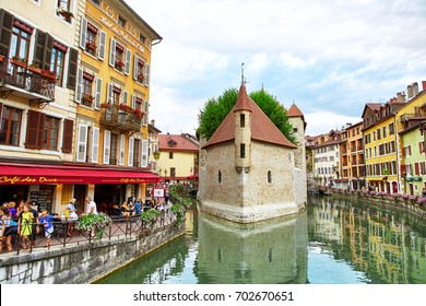 Annecy, France - JULY 19, 2017: People relaxing, walking, and eating around Palace of the Isle and river Thiou