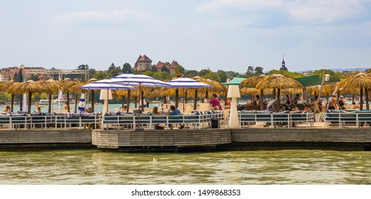 Annecy, France - July 2019 : Lake Annecy view with tourists lunching under the beach umbrellas of a restaurant on the banks of the lake