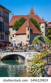 Annecy, France - July 2019 : Tourists visiting Annecy and the Palais de l'Isle situated on an island in the river Thiou. It mostly served as a prison and courthouse until the French Revolution