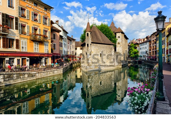 ANNECY, FRANCE - JUNE 22: People drink coffee near the River Thiou in Old Town, encircling the medieval palace perched mid-river - the Palais de l'Isle on June 22, 2014 in Annecy, France.
