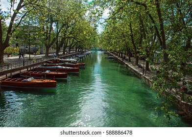 Annecy, France - June 30, 2016. Large canal with boats and trees in the city center of Annecy. An historical and lovely lakeside town located at the department of Haute-Savoie, south-eastern France.