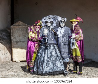 Annecy, France, March 16, 2014:  Portrait of four disguised people, posing in Annecy, France, during a Venetian Carnival which celebrates the beauty of the real Venice.