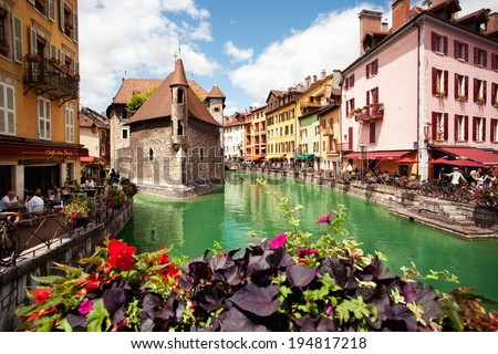 ANNECY, FRANCE - MAY 13: People walk around the River Thiou in Old Town, encircling the medieval palace perched mid-river - the Palais de l'Isle on May 13, 2012 in Annecy, France.