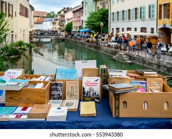 ANNECY, FRANCE - MAY 31, 2014 : Old  books display  on antique market over canal landscape of Annecy, France.