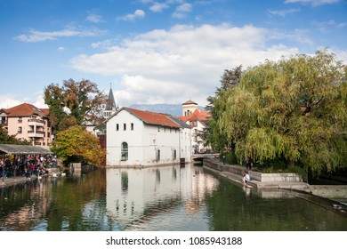 Annecy, France - October 2016: River Thiou, waterside building & spire  of Notre-Dame de Liesse, with young couple seated in the foreground. Tranquil scene, autumn colors and soft blue sky