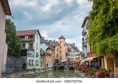 Annecy, France - October 2016: Tourists walk along the Thiou river, Annecy old town. Often called Venice of the Alps due to the beautiful medieval architecture, and canals.