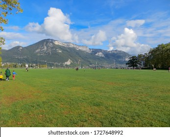 Annecy / France - October 5, 2019:  Lawns of the Champ de Mars (Field of Mars), Annecy lake, plane trees of the Albigny avenue, hills and mountain.