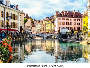 Annecy / France - October 5, 2019:  Flower-bedecked bridge with view of the Île palace (former prison) home to the Annecy History museum, Thiou canal, Île quayside and houses with colourful facades.