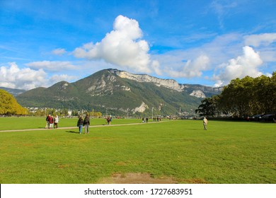 Annecy / France - October 5, 2019:  Lawns of the Champ de Mars, Annecy lake, plane trees of the Albigny avenue, hills and mountain.