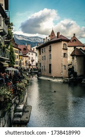 Annecy / France - October 5, 2019: Thiou canal, bridge Passage de l'Île, bank, the Quai de l'Eveche, Ile palace (former prisons) and houses with colorful facades in the old town.