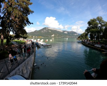 Annecy / France - October 5, 2019: Lake Annecy view with tourists walking on the Promenade Jacquet and on the Europe gardens, boats and mountains in the background.