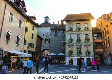 Annecy / France - October 5, 2019:  Sainte-Claire square with the Maison Gallo, arcaded houses and colourful facades, Sainte-Claire gate, clock and café terrace.