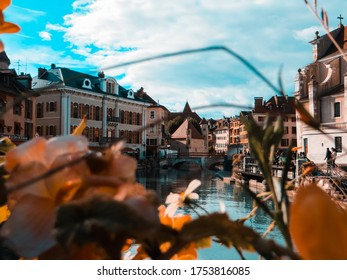 Annecy / France - October 5, 2019:  Flower-bedecked bridge with view of the Ile palace (former prison) home to the Annecy History museum, Thiou canal, Île quayside and houses with colourful facades.