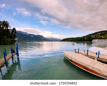Annecy / France - October 5, 2019: Bank of the Europe gardens, moored boats, Annecy lake and mountains mountain of La Tournette and the sharp rocky ridges of the Dents de Lanfon.