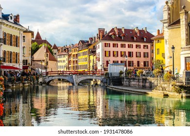 Annecy, France - October 5, 2019:  Flower-bedecked bridge with view of the Ile palace (former prison) home to the Annecy History museum, Thiou canal, Île quayside and houses with colourful facades.