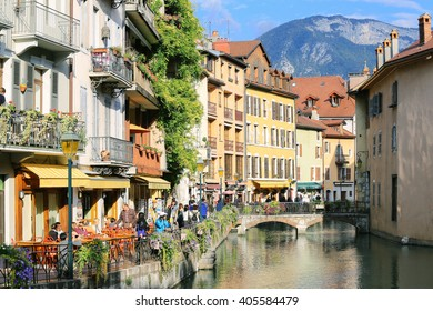 Annecy, France - Sep 29 2015: People drink coffee near the River Thiou in Old Town, encircling the medieval palace perched mid-river - the Palais de l'Isle