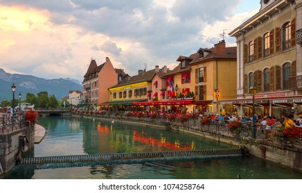 ANNECY, FRANCE - SEPTEMBER 2016 People sitting at street cafe and walking along Le Thiou river in Annecy France at late evening. The area has many bars, restaurants and is a popular tourist attraction