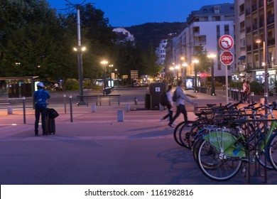 ANNECY, HAUTE SAVOIE / FRANCE August 15, 2018: in front of the Annecy bus station, walkers, passers-by, travelers and bicycles, at nightfall in August,