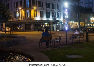 ANNECY, HAUTE SAVOIE / FRANCE AUGUST 08 2018: at nightfall, the station area, the last walkers enjoy the cool evening under the romantic lights ready fountains