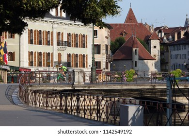 ANNECY, HAUTE SAVOIE / FRANCE JUILY 22 2018: from the quays of tourist boats, view of the palace of the island and the old town in the morning light, a cyclist passes on the empty deck of cars.