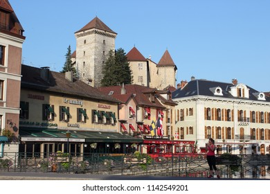 ANNECY, HAUTE SAVOIE / FRANCE JUILY 22 2018: from the quays of the boats, morning view on the old castle and the brasserie and restaurant on the edge of the thiou, a jogger on the bridge