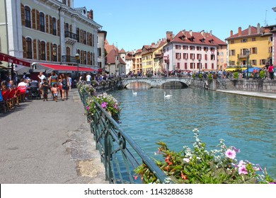 ANNECY, HAUTE SAVOIE / FRANCE JULY 22 2018: wide and pitoresque view at the edge of thiou and the canals where flanks swans, overlooking the old town of annecy, tourists enjoy the beautiful day