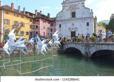 ANNECY, HAUTE SAVOIE / FRANCE JULY 22 2018: tourists no longer know where to give pictures with the old buildings of the old town and the work of the artist Antoine Milian, flying fish giant origami
