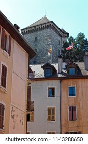 ANNECY, HAUTE SAVOIE / FRANCE JULY 22 2018: from the streets of the old town, view of the castle tower and its flags fluttering in the wind