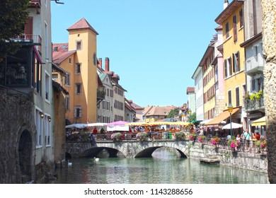 ANNECY, HAUTE SAVOIE / FRANCE JULY 22 2018: typical view of the old town and canals, market day on the Morens bridge under the blue summer sky