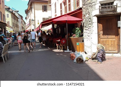 ANNECY, HAUTE SAVOIE / FRANCE JULY 22 2018:   alone with her bags, lying on the ground at the beginning of a restaurant of the old city. The tramps also exist in the Annecy city