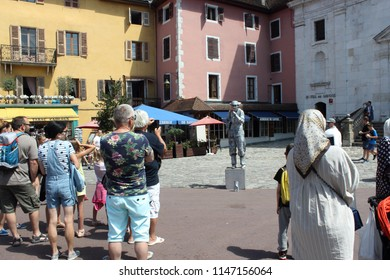 ANNECY, HAUTE SAVOIE / FRANCE JULY 22 2018: Passersby stop for a moment to admire the work of the street artist in full representation under a blazing sun